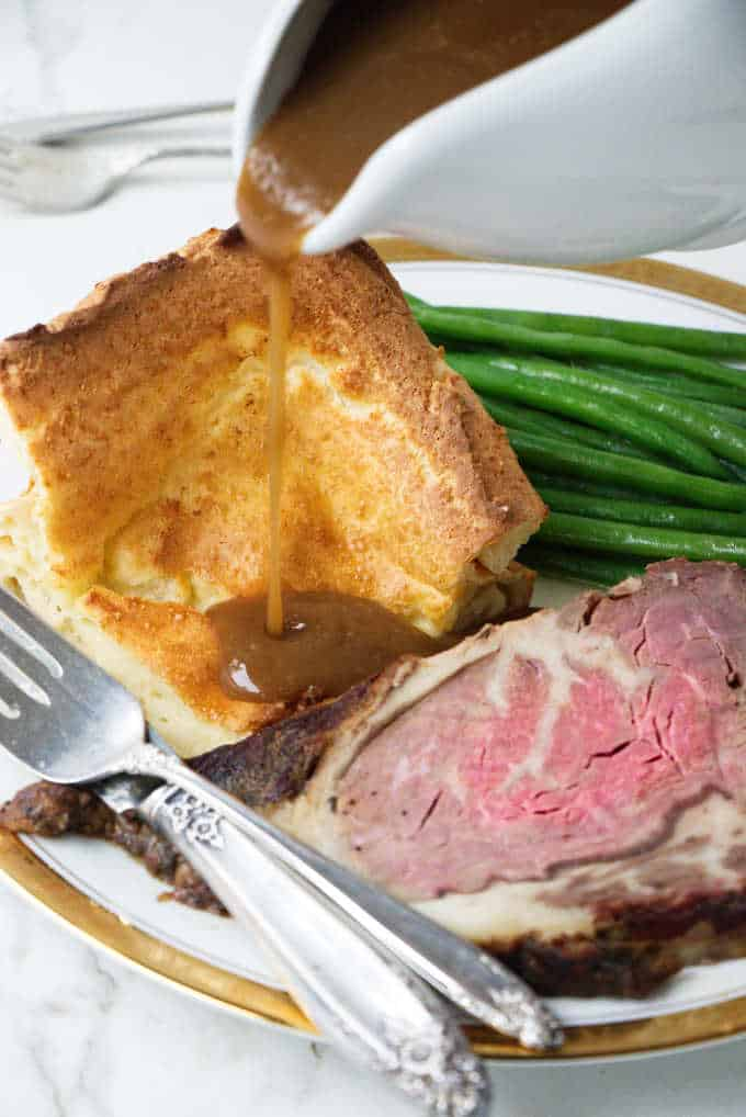 Yorkshire Pudding with a gravy pour, slice of beef and green beans