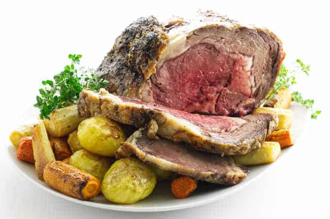 Sliced rib roast on platter with roasted vegetables