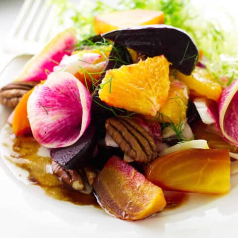Serving of beet salad on plate with fork and napkin