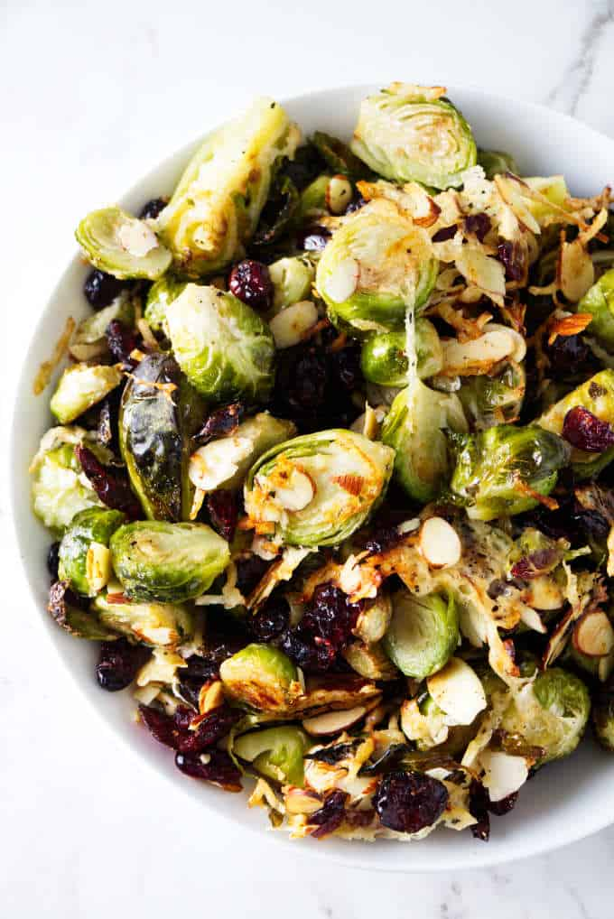 A serving bowl of roasted Brussels sprouts with parmesan, cranberries, and almonds