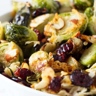 A bowl of roasted Brussels sprouts with parmesan, cranberries, and almonds