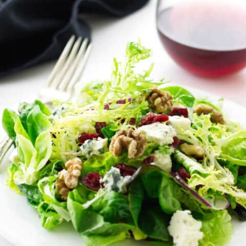Salad on a plate with fork, napkin and wine in the background