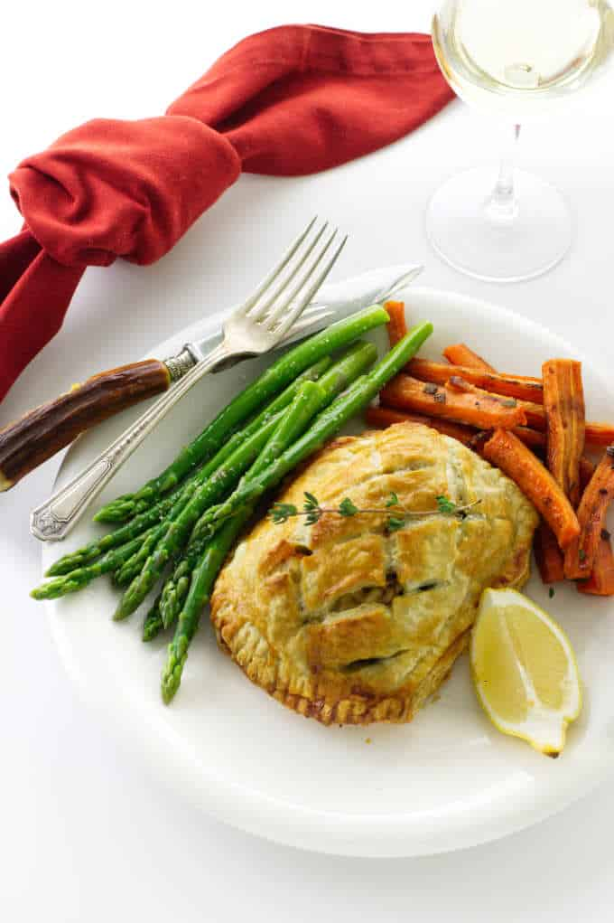 Overhead view of salmon and crab wellington with asparagus, carrots, lemon wedge and a glass of wine