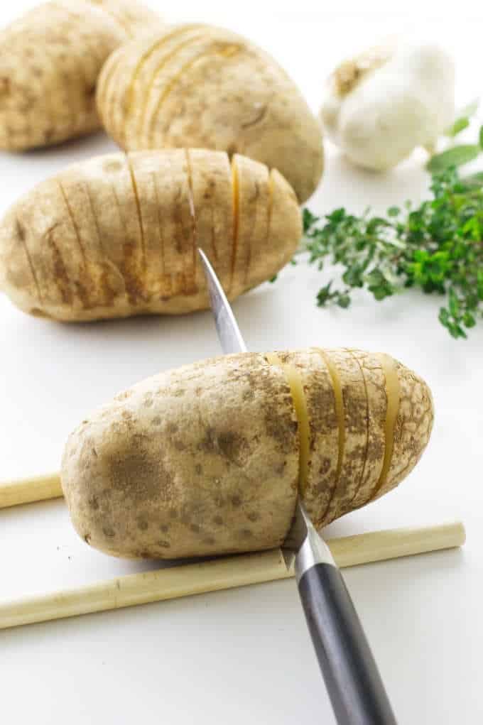 Large potatoes being prepared/sliced for hasselback potatoes