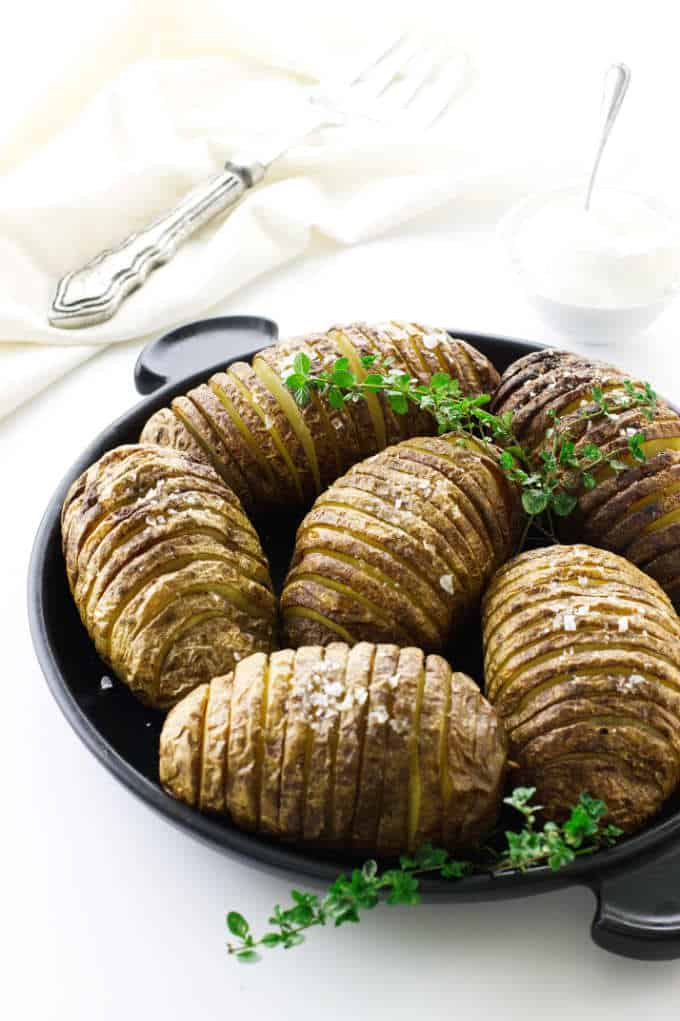 Plate with six prepared garlic-butter hasselback potatoes