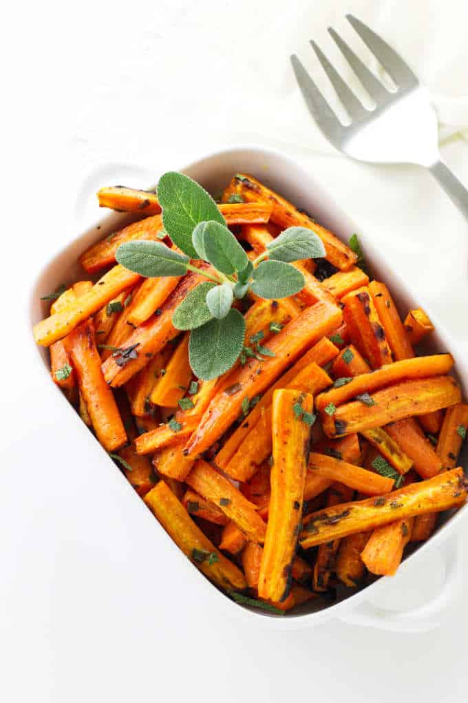Overhead view of honey roasted carrots with fresh sage