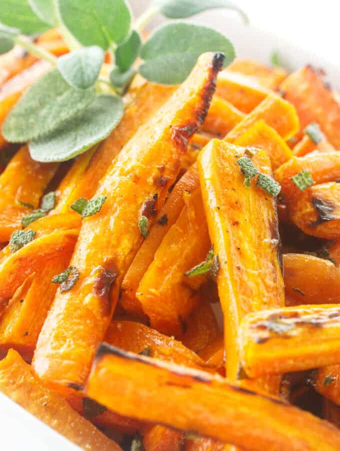 Close up photo of roasted carrots, garnished with fresh sage