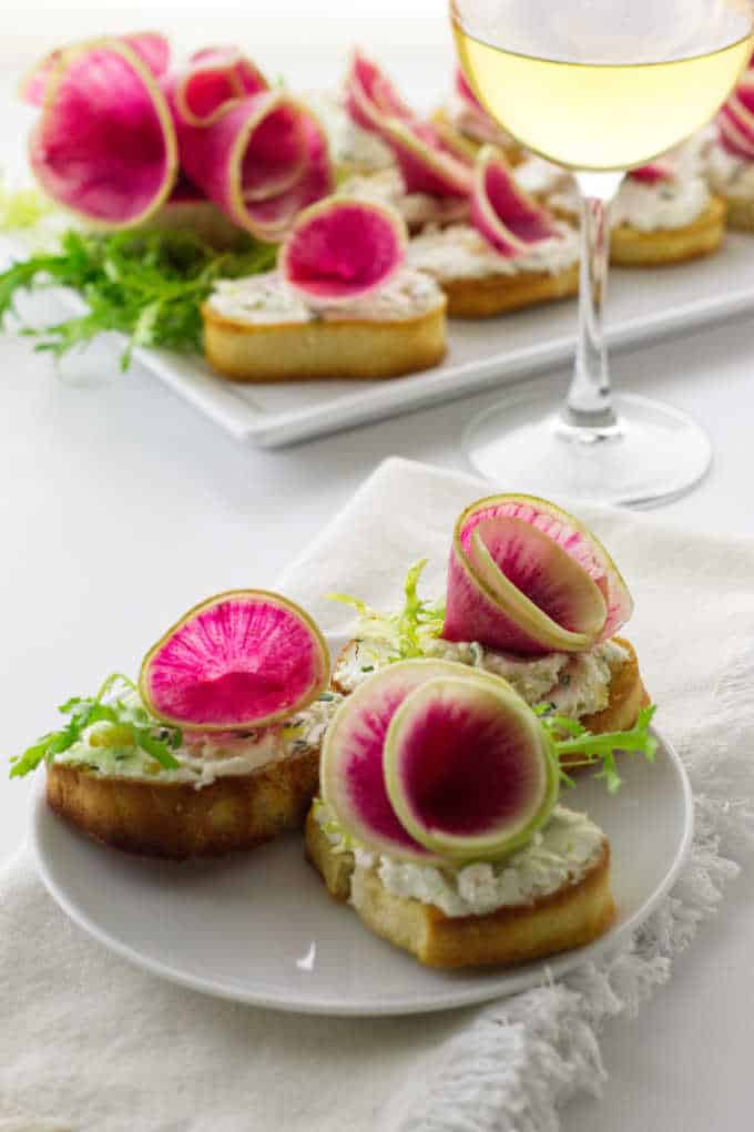 three watermelon radish and goat cheese crostini servings on plate with a plate in background and glass of wine