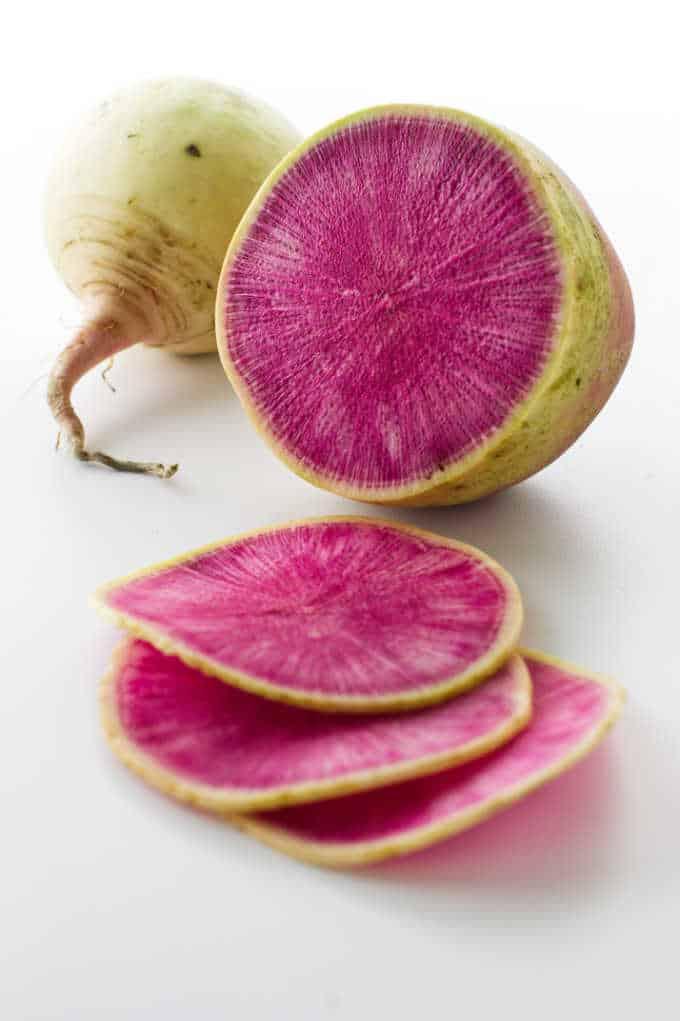 Watermelon radish slices, a cut watermelon radish and small uncut radish