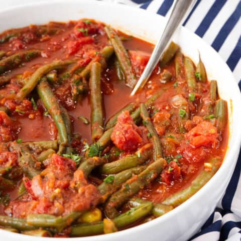 instant pot Lebanese green beans in a serving dish with a spoon
