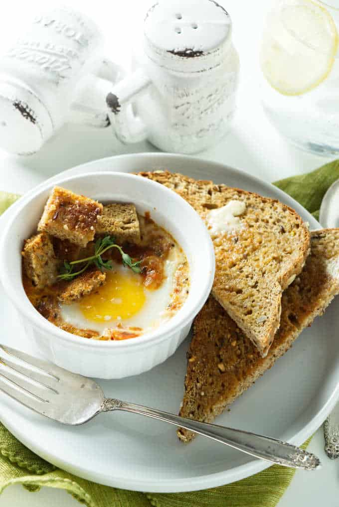A serving of baked eggs with tomatoes in an individual ramekin.