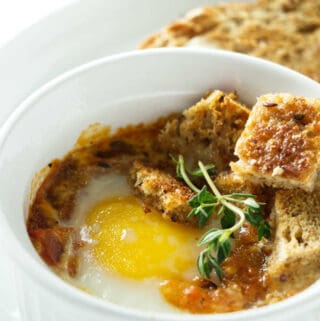 A baked egg with tomatoes in a white ramekin.