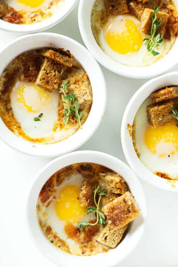 Overhead shot of ramekins with baked eggs and tomato