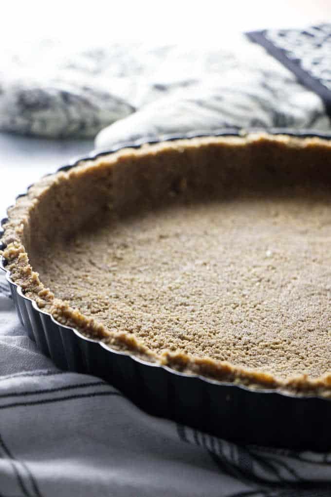 A brown sugar pecan pie crust in a tart pan.