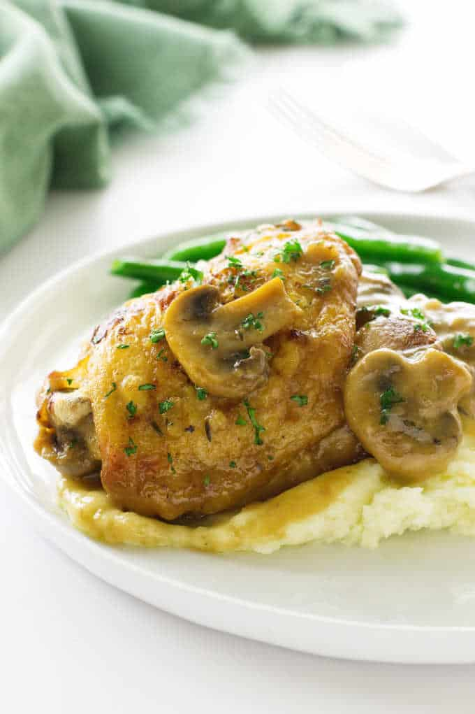 Chicken in mushroom cream sauce on a plate with mashed potatoes