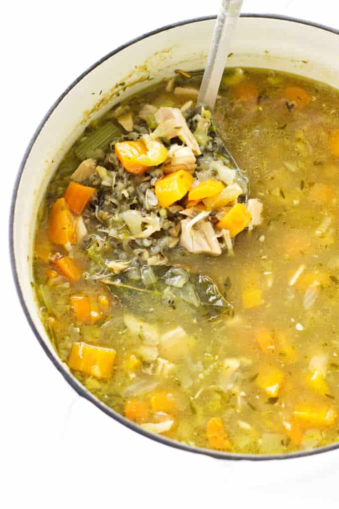 A stock pot of chicken soup with wild rice and vegetables.