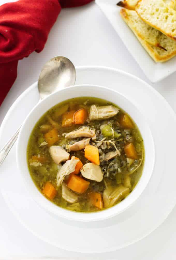 A bowl of vegetable chicken soup with wild rice and a plate of bread.