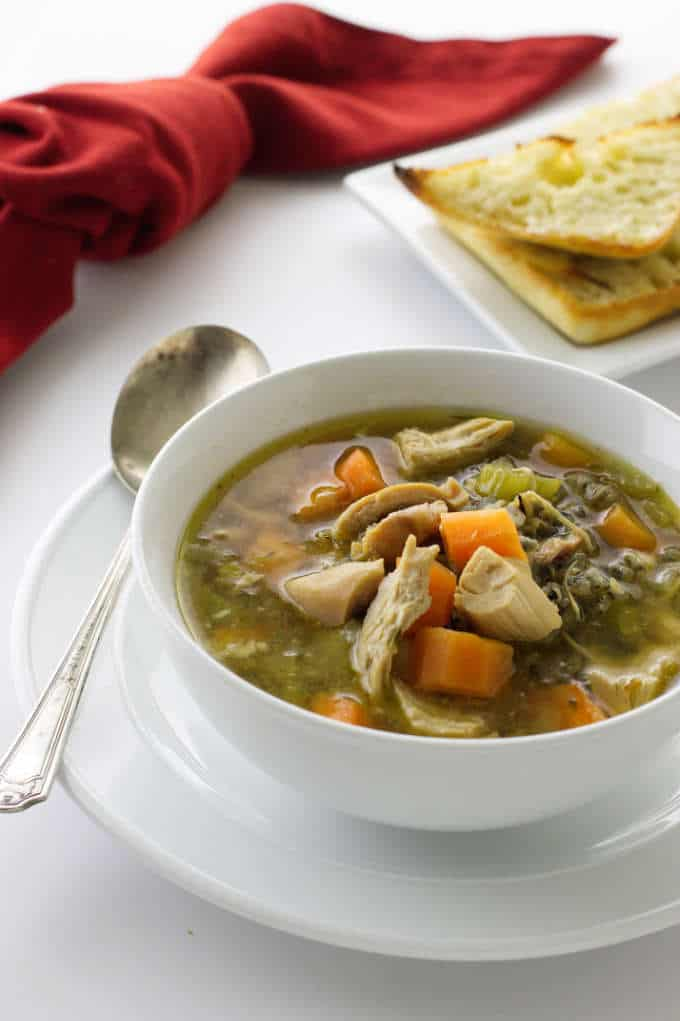 Chicken soup with wild rice and vegetables in a serving bowl.