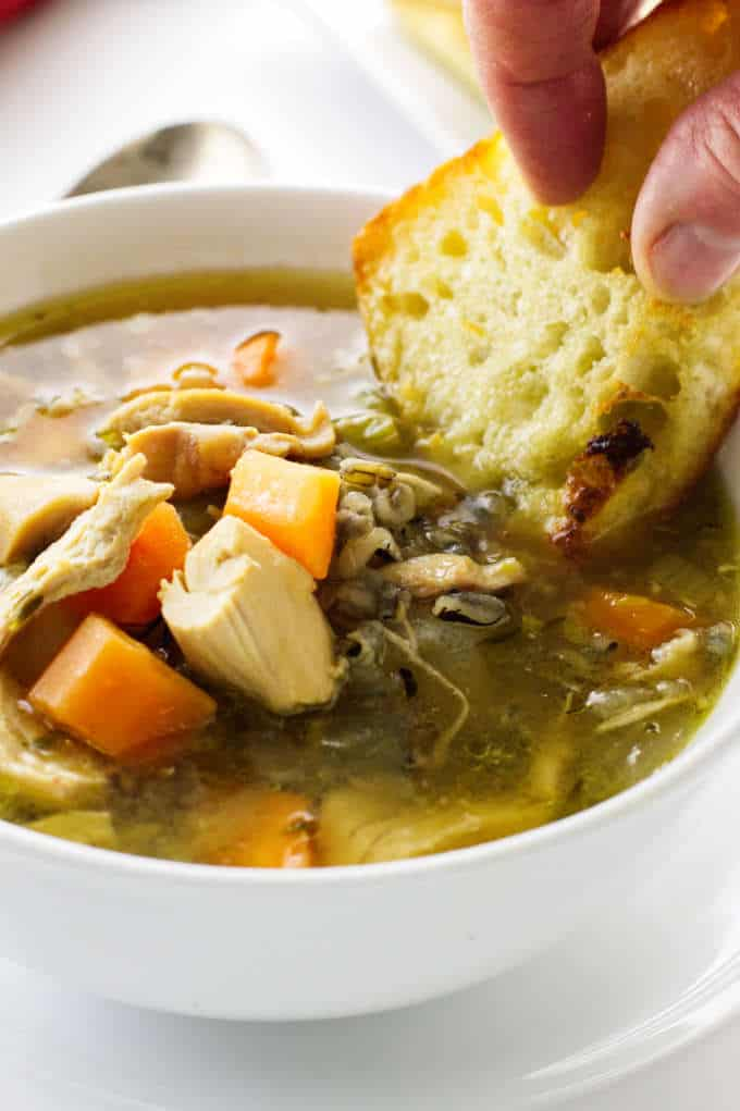 Dunking bread into a bowl of chicken soup with wild rice.