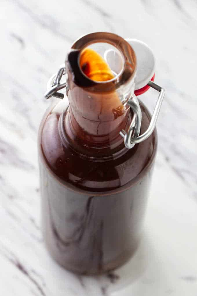 Homemade chocolate syrup in a tall bottle.