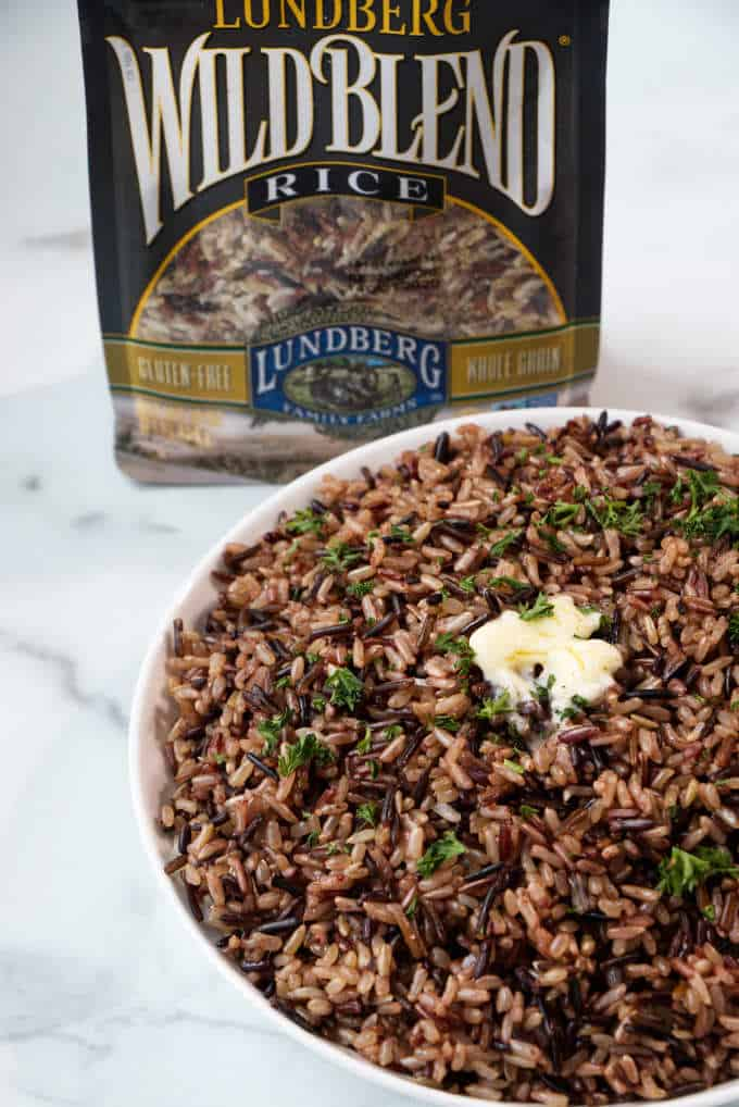 A dish of wild blend rice with a package of Lundberg wild rice blend.