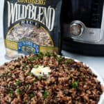 A bowl of wild blend rice with a bag of Lundberg wild rice blend and an instant pot in the background.