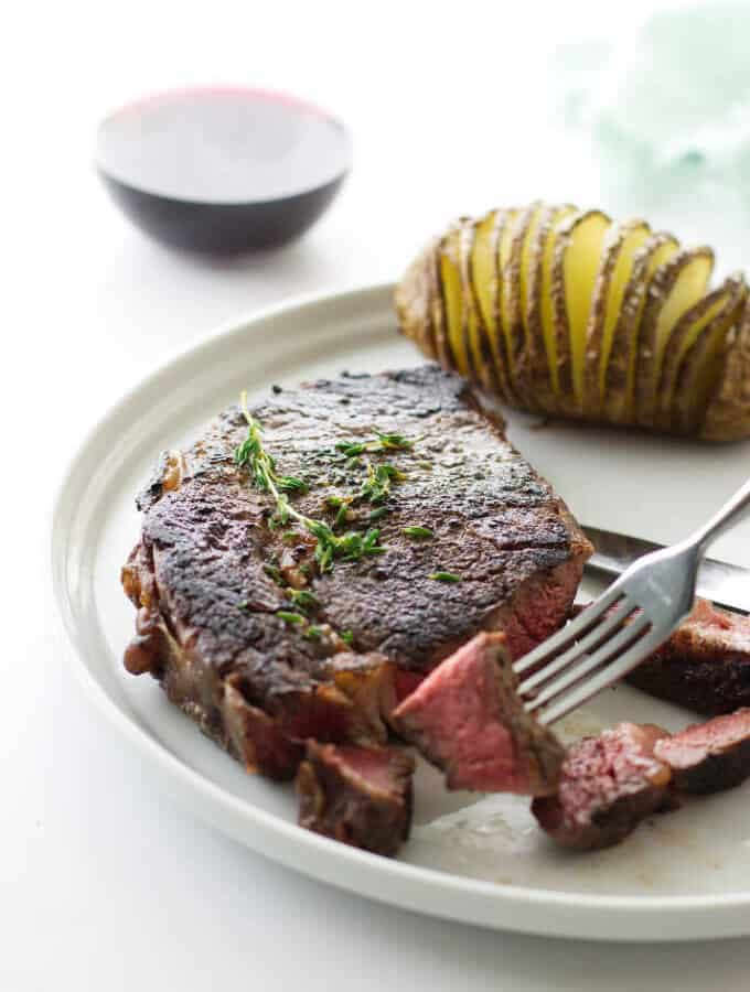 Ribeye steak with fork holding a bite, hasselback potato and glass of wine in background