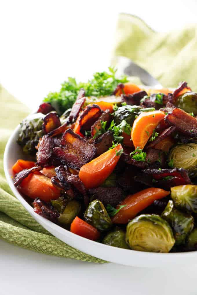 A serving bowl of roasted Brussel sprouts and carrots.
