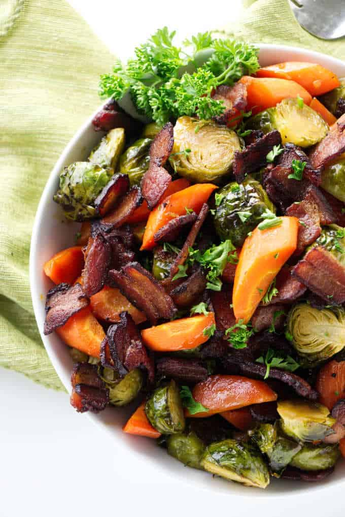 Roasted Brussels Sprouts with carrots and bacon in a bowl.