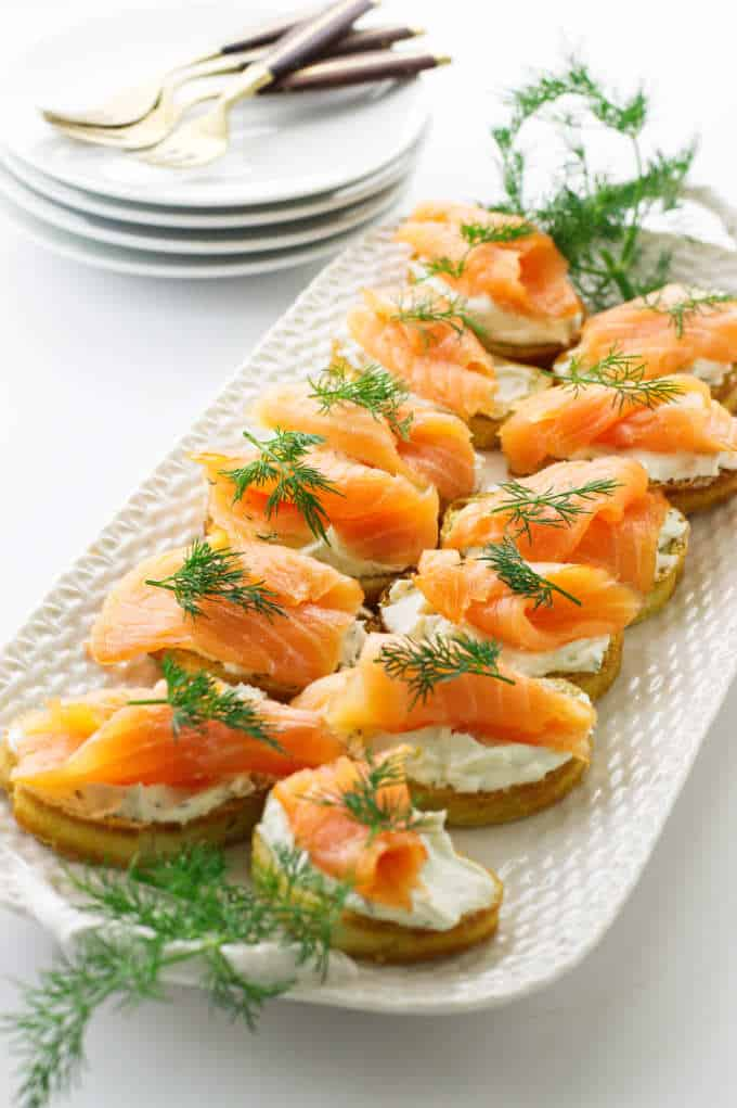 Platter of smoked salmon crostini, appetizer plates/forks in background