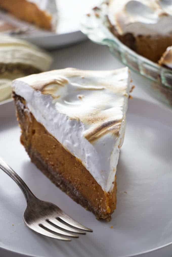 A closeup of a slice of Southern sweet potato pie with toasted marshmallow fluff on top.