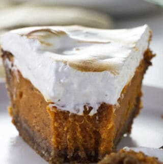 A closeup of a partially eaten Southern sweet potato pie with homemade marshmallow fluff.