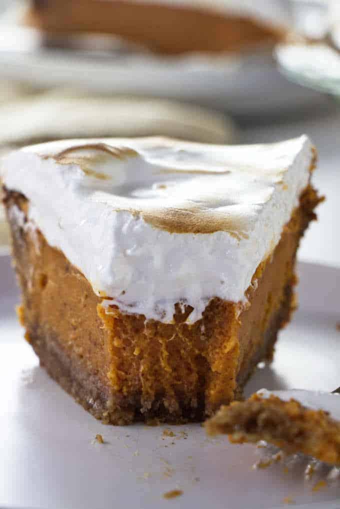 A closeup of a partially eaten Southern sweet potato pie with homemade marshmallow fluff.