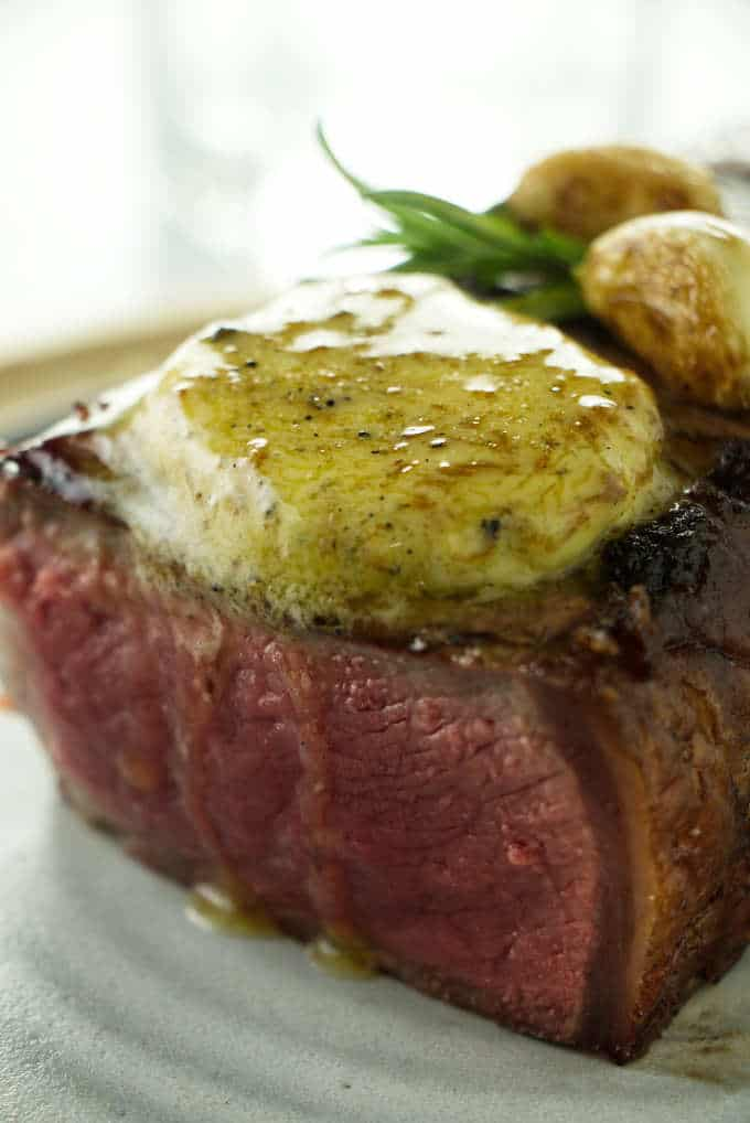 A steak with a pat of melting truffle butter.