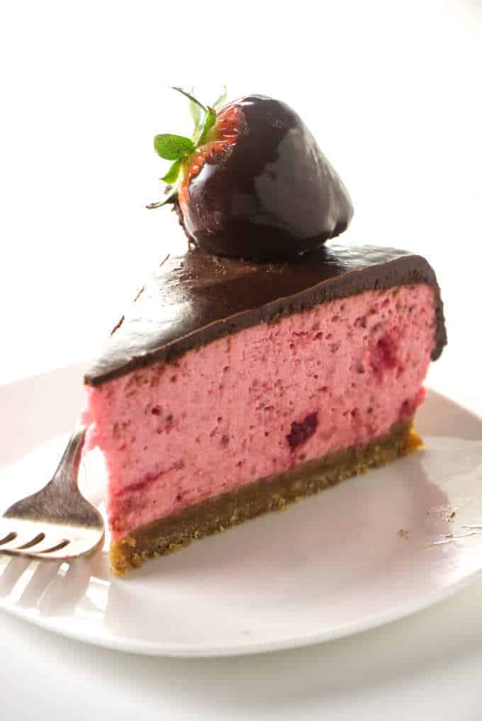 A slice of no-bake strawberry cheesecake covered in chocolate.