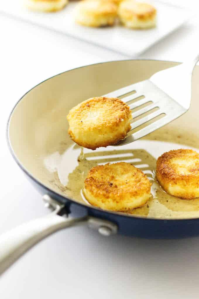 Breaded Goat cheese discs in skillet with spatula