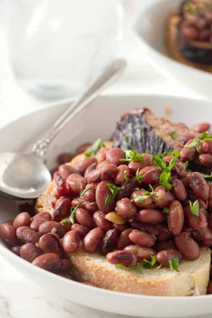 A serving of red beans and ham on a slice of sourdough bread.