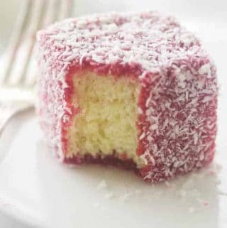 close up of a serving of raspberry lamington on a plate with fork