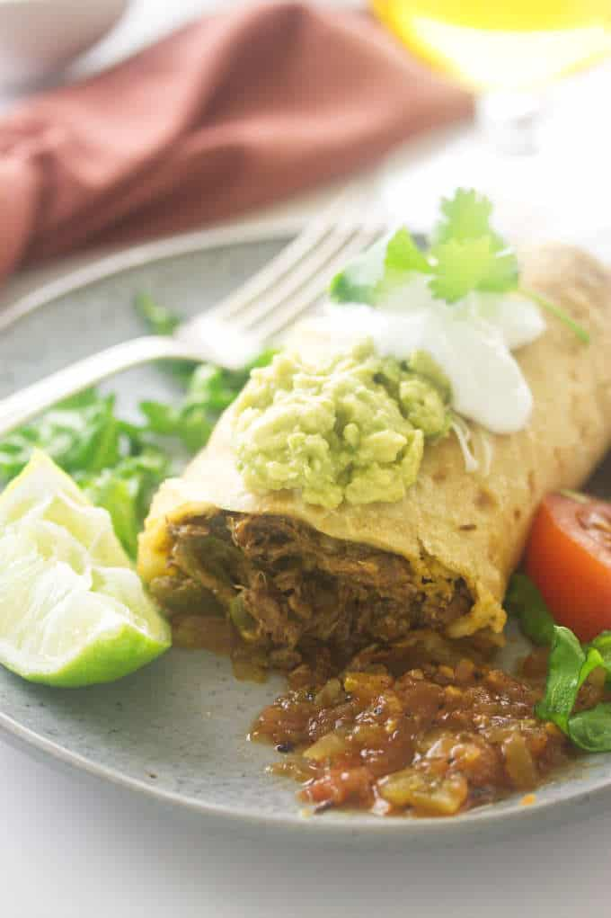 A shredded beef chimichanga on a plate with salsa and a slice of lime.