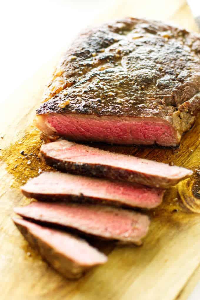 sliced ribeye steak on cutting board