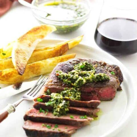 ribeye steak with chimichurri sauce on plate with fork and fries. Background dish of chimichurri sauce and glass of wine