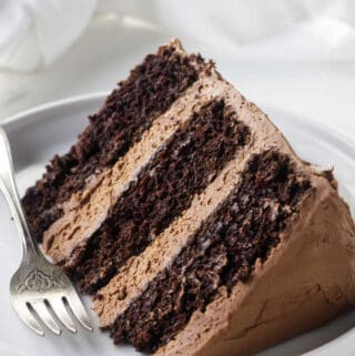 A slice of chocolate cake with chocolate buttercream frosting.