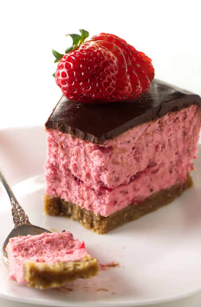 A partially eaten strawberry cheesecake with chocolate on top.