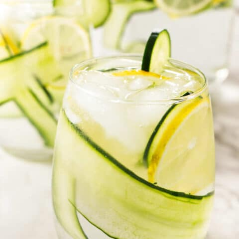 A glass of cucumber lemon water with a pitcher in the background.