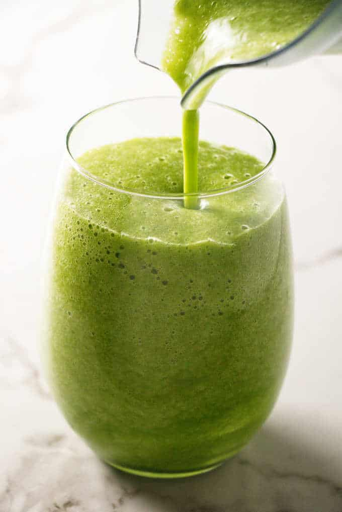 Pouring a green smoothie into a glass.