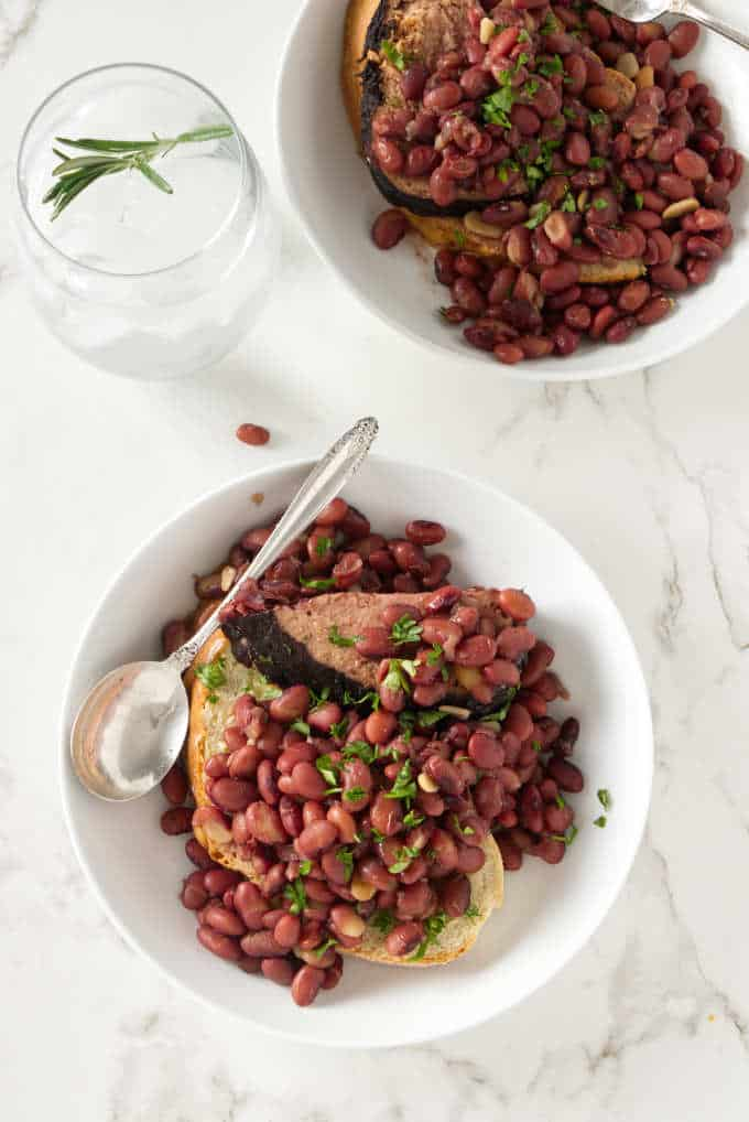 Two servings of red beans and ham in shallow bowls.