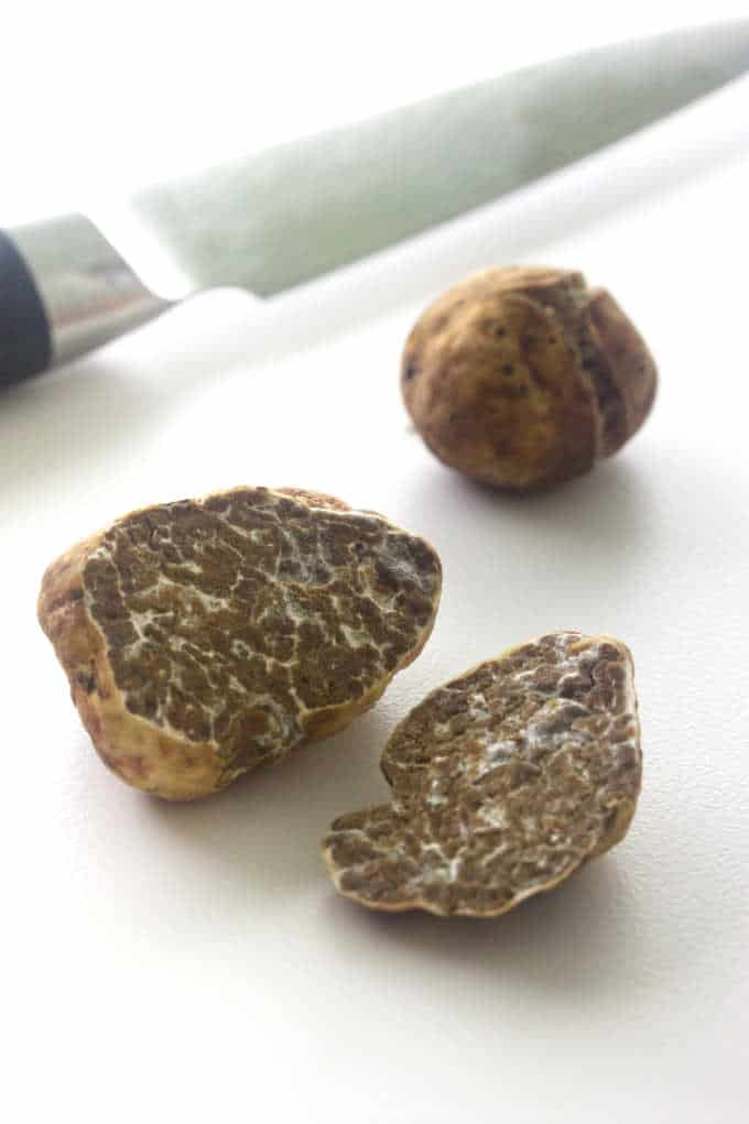 Oregon white truffle cut in half, small whole truffle, knife in background