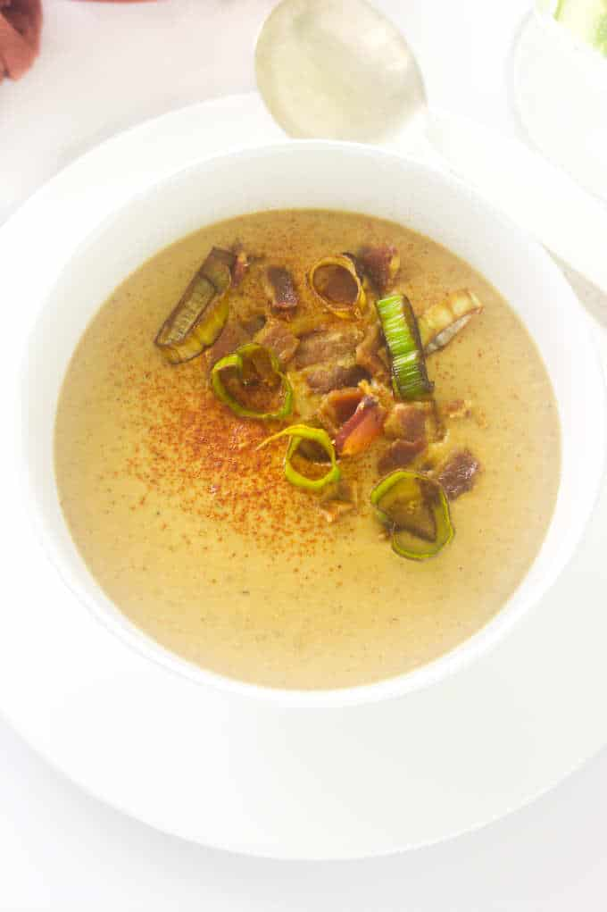 Overhead view of roasted cauliflower soup garnished with paprika, bacon bits and crisp fried leek rings