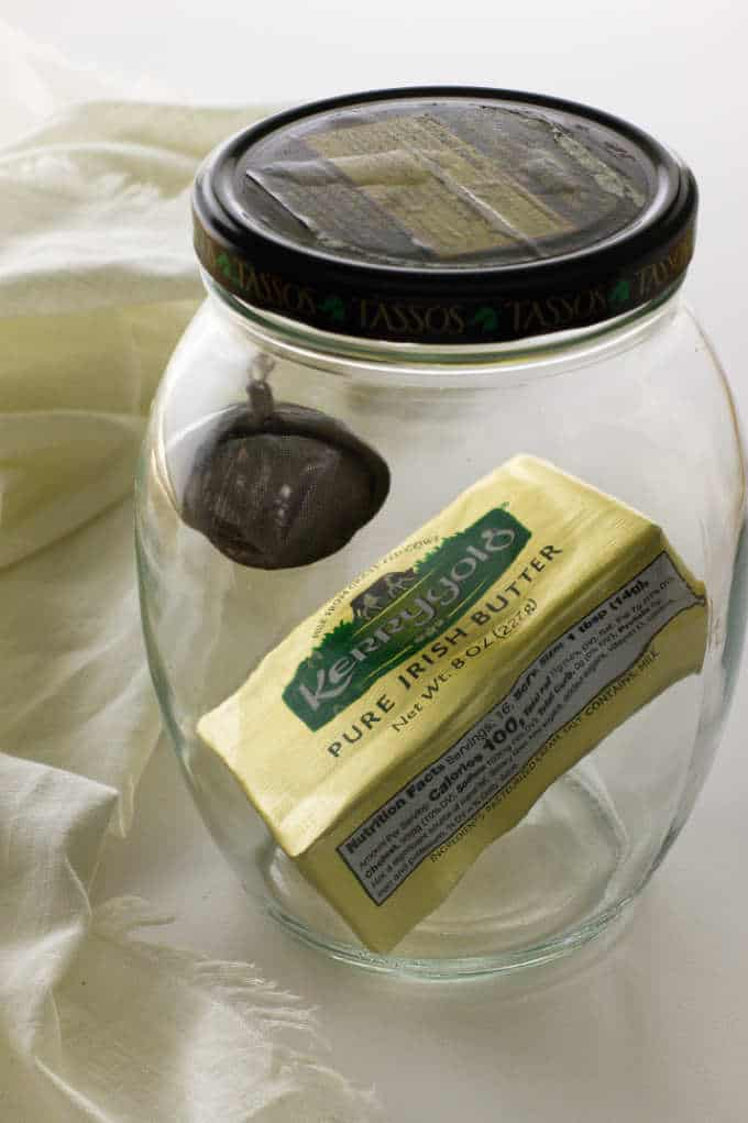 A block of butter in a jar with a black truffle for gas infusion.