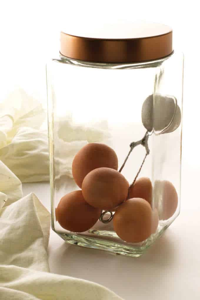 5 eggs in a jar with a black truffle in a tea infuser to infuse the eggs with black truffle flavor.